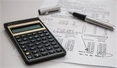 photo of calculator, pen and paper representing taxes