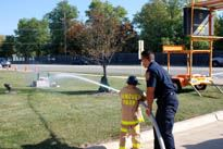 Fireman Helping Child with Fire Hose